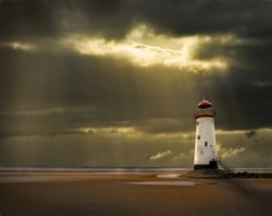 lighthouse on north wales coast illuminated in the golden afterglow of a storm at sea