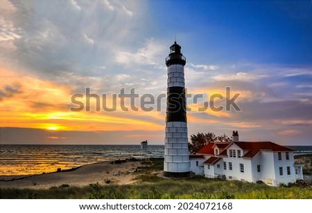 Lighthouse on the beach at sunset. Sea lighthouse at sunset. Sunset lighthouse view. Lighthouse at sunset