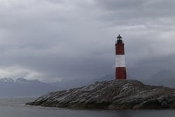 Lighthouse on the end of the world, famous sign in the beagle channel, red and white house to orientate on the ocean, landmark near by the coastline in tierra de fuego patagonia argentina