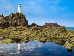 Lighthouse on the rock and reflection. Jersey, Channel Islands