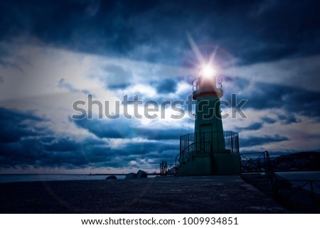 Lighthouse on the sea at night, cloudy sky