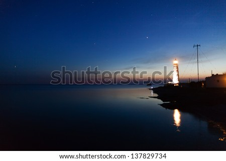 Lighthouse on the water edge near sea at night
