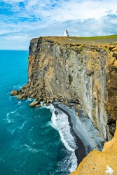Lighthouse on top of Icelandic cliff overlooking the sea