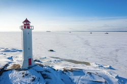 Lighthouse on winter island. Sea frozen fairway with ships in the background.