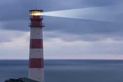 Lighthouse searchlight beam through marine air