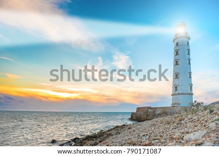 Lighthouse searchlight beam through sea air at night. Seascape at sunset