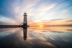 Lighthouse standing in pool of water stunning sunset sunrise reflection reflected in water and sea steps up to building north Wales seashore sand beach still water orange glow golden hour blue hour