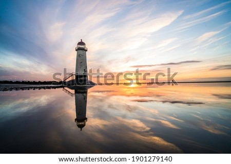 Lighthouse standing in pool of water stunning sunset sunrise reflection reflected in water and sea steps up to building north Wales seashore sand beach still water orange glow golden hour blue hour Foto stock ©
