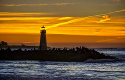 Lighthouse sunset silhouette. Sea shore lighthouse sunset silhouette. Sunset sea shore lighthouse silhouette. Sea shore lighthouse at sunset