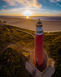 Lighthouse texel Netherlands, Dutch lighthouse Holland, red light house at the beach from above drone view