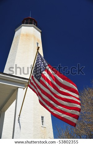 Lighthouse tower and american flag blowing in wind