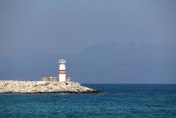 Lighthouse tower on a stone pier in azure sea against misty mountains