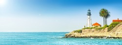 lighthouse tower on cliff in ocean landscape against stormy sea water and blue sky background. Panorama ultra wide side view of marine light beacon with palm tree located on rock. Copy space banner
