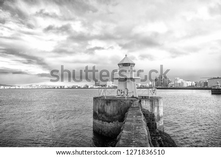 Lighthouse tower on stone pier in reykjavik, iceland. Lighthouse in sea. Seascape and skyline on cloudy sky. Architecture structure and design. Navigational aid concept. Wanderlust and travelling. #1271836510