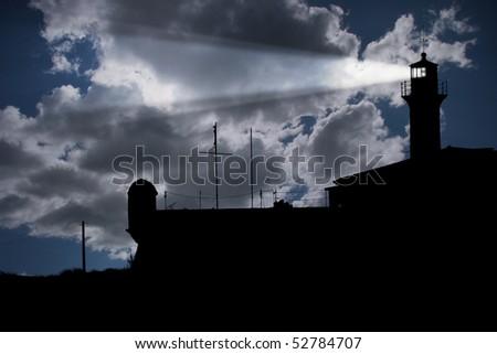 Lighthouse under dark cloudy sky - stock photo