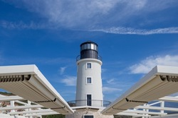 Lighthouse  watch tower - tall round building with light beacon warning signal on top, for the safety of nautical navigation at sea or ocean, under clouds in blue sky on a sunny day.