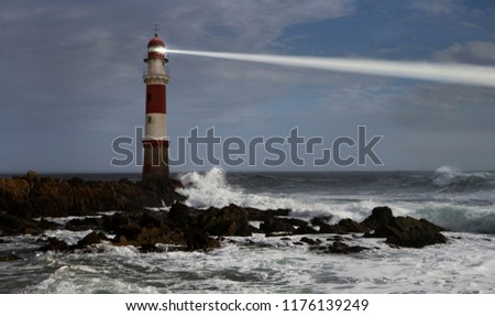 Lighthouse with beam over rough seas