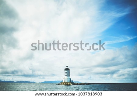 Lighthouse with cloudy skies.  #1037818903