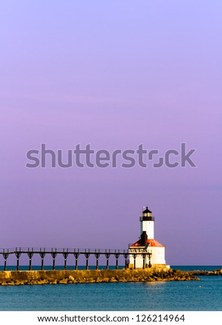 Lighthouse with its distinctive elevated catwalk at Michigan City, Indiana on Lake Michigan just after sunrise wit purple sky.