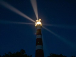 Lighthouse with light rays during night, a starry sky on the island of Ameland, Hollum, Netherlands.