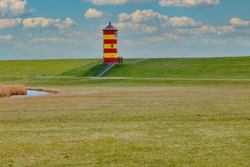 Lighthouse with red and yellow stripes on a green dike. Lighthouse on the North Sea. Green dike with green lawn