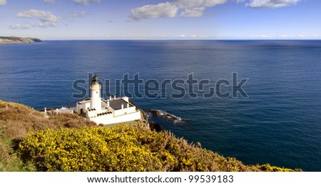 Lighthouse with Yellow shrub bush and sea in background. Sunny day in Douglas on the Isle of Man