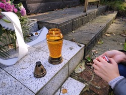 Lighting a grave candle in Poland. The week before All Saints Day (Polish: Wszystkich Swietych) in a cemetery in Bytom.