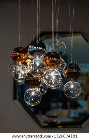 Lighting balls on the chandelier in the lamplight, light bulbs hanging from the ceiling, lamps on the dark background. #1326094181