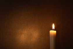 Lighting candle against canvas background with free space for text