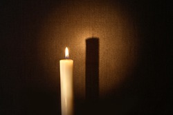 Lighting candle with long shadow against canvas background
