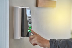Lighting glowing on wall while young man or woman use left hand scan finger print for enter security systems.