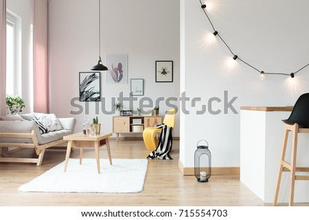 Lighting in bright living room with striped blanket on yellow chair next to table on white carpet