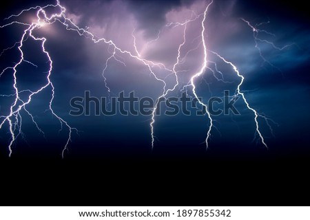 Lighting in the sky during storm at night