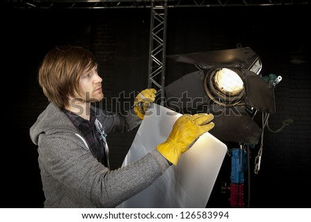 Lighting man placing diffuser on a studio light in a Television studio.