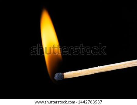 Lighting matches at the moment when it explodes. Burning wooden match over black background. Close up. Copy space.