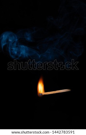 Lighting matches at the moment when it explodes. Burning wooden match with blue smoke over black background. Close up. Copy space.