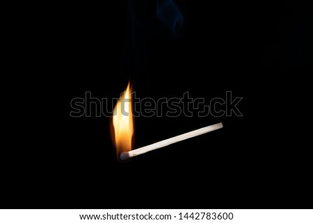 Lighting matches at the moment when it explodes. Burning wooden match with smoke over black background. Close up. Copy space.
