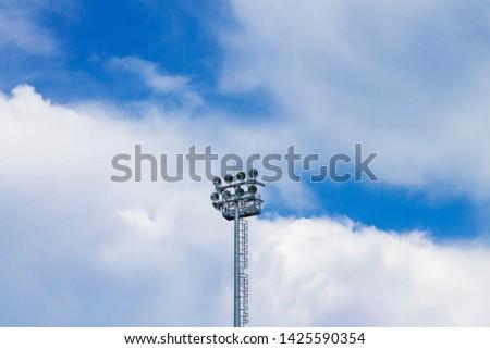 Lighting spotlights sports stadium against the blue sky. #1425590354