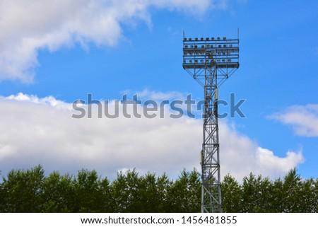 Lighting support. Stadium Post Lighting. Tall pillar with spotlights to illuminate a football stadium against the sky with clouds