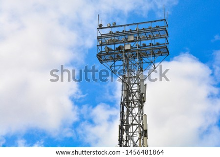 Lighting support. Stadium Post Lighting. Tall pillar with spotlights to illuminate a football stadium against the sky with clouds #1456481864
