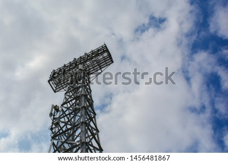 Lighting support. Stadium Post Lighting. Tall pillar with spotlights to illuminate a football stadium against the sky with clouds