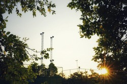 Lighting towers in a tennis court in late afternoon