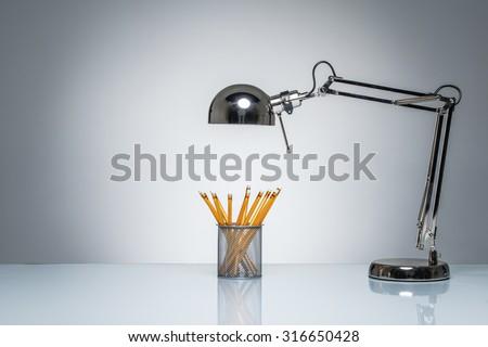 lighting up orange pencil holder stationery with desk lamp on round studio lighting