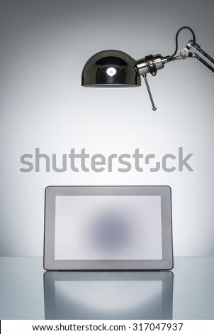 lighting up tablet touchpad note with desk lamp on round studio lighting