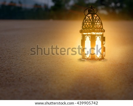 lighting with candle inside Lantern shining on sand floor playground, children play with it in Ramadan night, also known and called as Ramadan Kareem Lantern