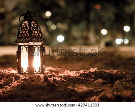 "lighting with candle inside Lantern shining on sand floor playground, children play with it in the night, also known as ""Ramadan Kareem Lantern"""