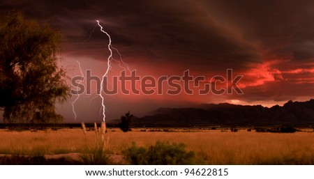 Lightning against dramatic red sunset clouds during desert summer thunderstorm/Desert Grassland with Lightning Thunderstorm and Red Sunset/Lightning and red sunset during monsoon summer thunderstorm