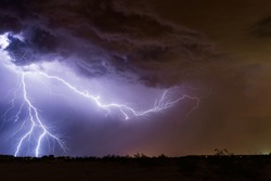 Lightning bolt strike and dramatic storm clouds over a city