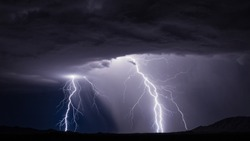 Lightning bolt strike from a thunderstorm with rain and dramatic storm clouds