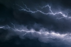 Lightning bolts crawl through the sky just below the anvil of a severe thunderstorm over the great plains in the USA.
